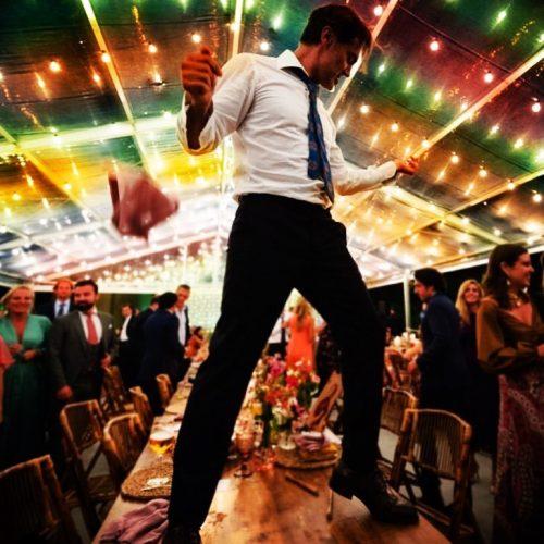 Novio de boda bailando encima de una mesa